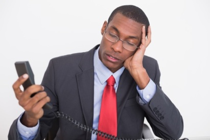 Young tensed young Afro businessman with telephone receiver against white background